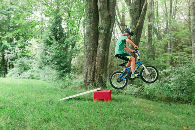 Boy jumping ramp with bicycle