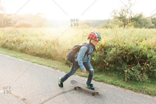 Young boy skateboarding to school