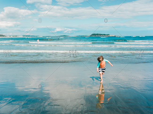 Young boy running on the beach