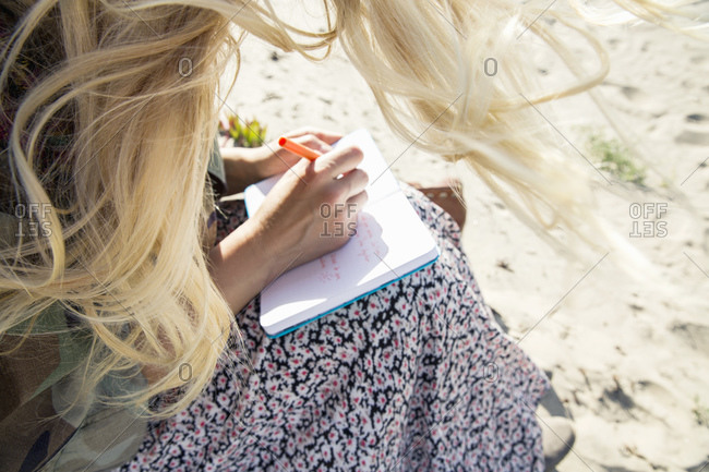Woman writing in journal/diary outdoors