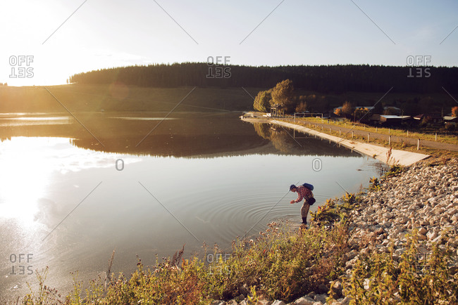 Man washing his hands in a lake