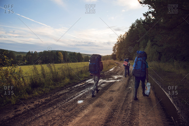 Backpackers walking on a muddy dirt road