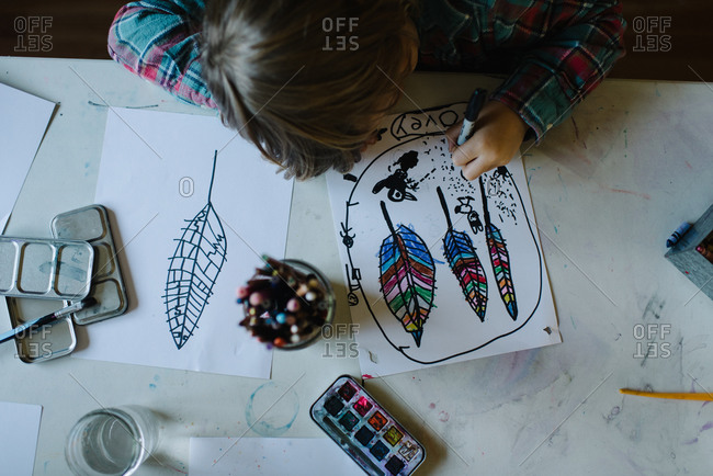 Overhead view of a little boy coloring pictures