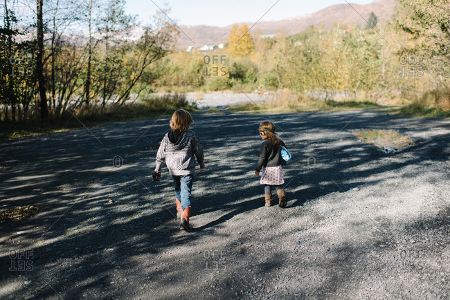 Brother and sister walking together on a gravel path