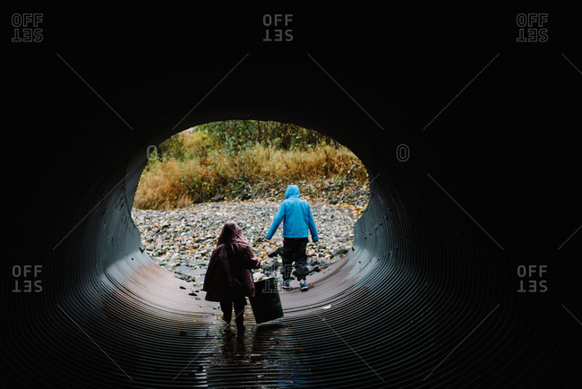 Brother and sister walking through a storm drain
