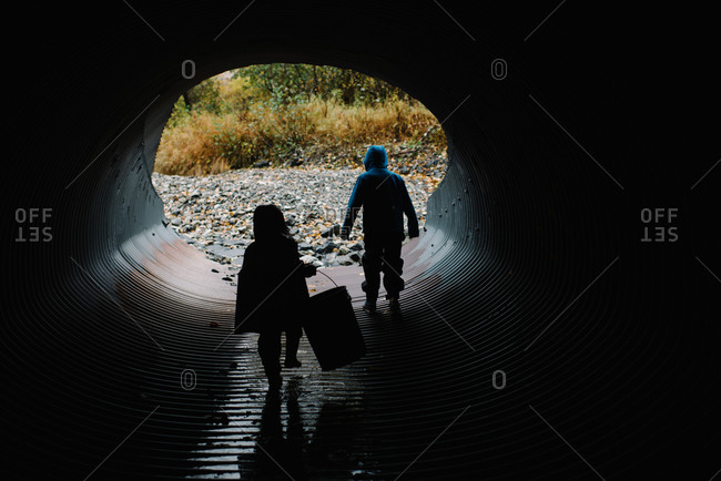 Brother and sister exploring a storm drain