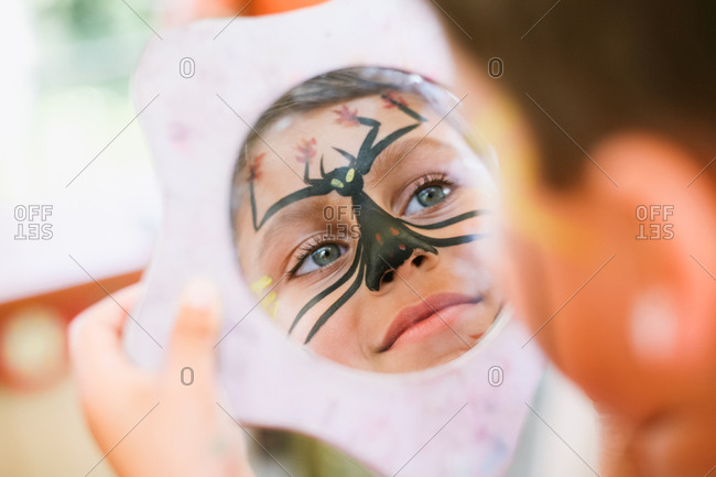 Young boy smiles at his painted face in mirror