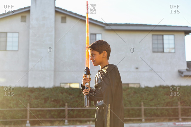 Young boy plays outdoors with toy lightsaber