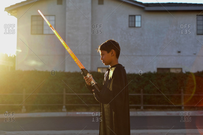 Costumed young boy playing with toy lightsaber