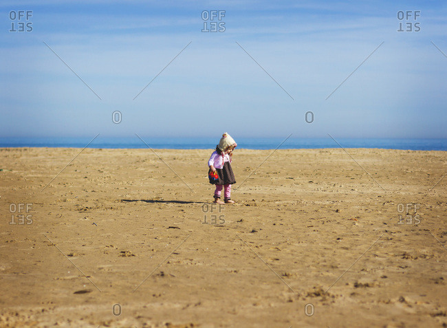 Toddler girl standing barefoot on beach with toy