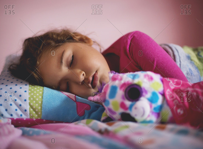 Portrait of a young girl asleep in bed with plush unicorn