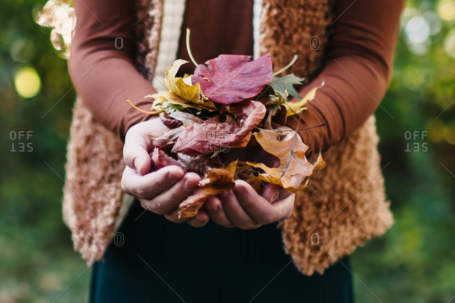 Woman in a fur vest holding autumn leaves