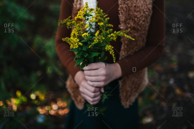 Woman in a fur vest holding yellow flowers