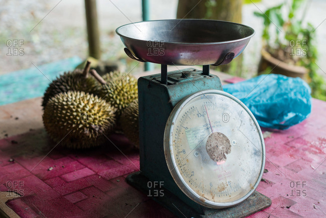 Durian fruit and a scale on table at outdoor market