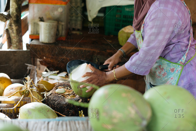 Woman cutting coconuts at market