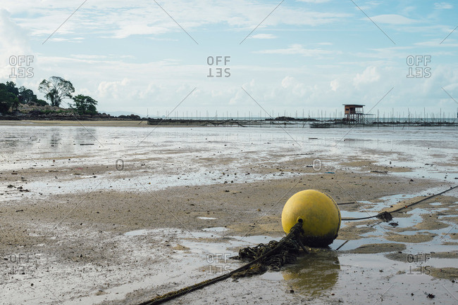 Rope bouy on beach at low tide in Malaysia