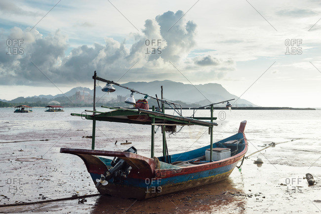 Fishing boat on beach at low tide in Langkawi, Malaysia