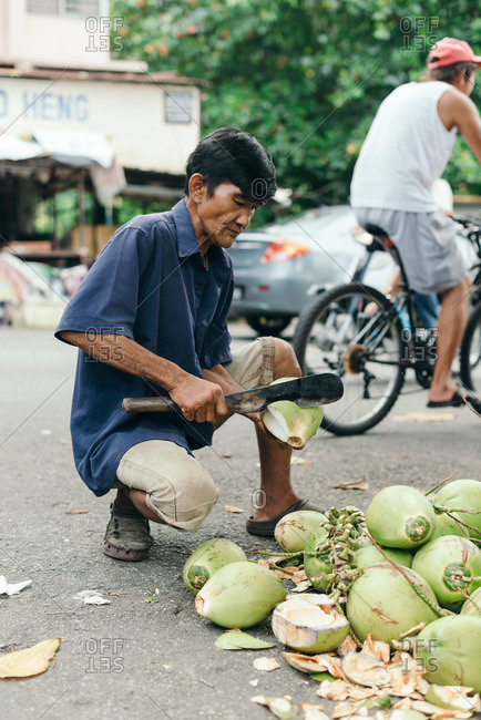Malaysia - July 5, 2015: Man cutting coconut in street at outdoor market
