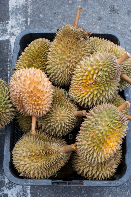 Bin of fresh durian fruits at a produce stall in an outdoor market