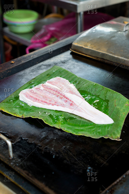 Grill with fresh fish fillet being cooked on banana leaf