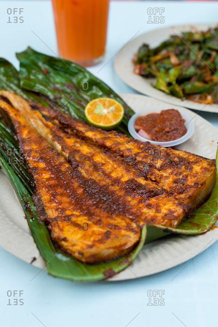 Fresh grilled stingray served on banana leaf at Penang street market