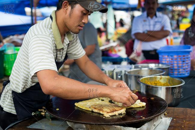 Brinchang, Pahang, Malaysia - July 6, 2015: Man cooking local specialty stuffed pancakes called murtabak at street market