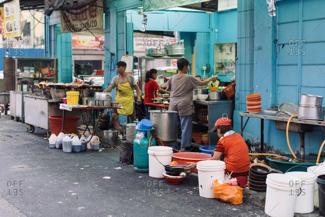 Kuala Lumpur, Malaysia - July 11, 2015: Vendors preparing food at outdoor market