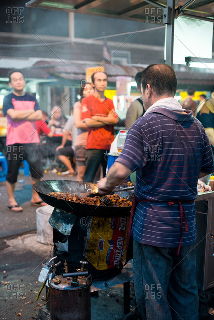 Man stirring food in outdoor cooker at street market