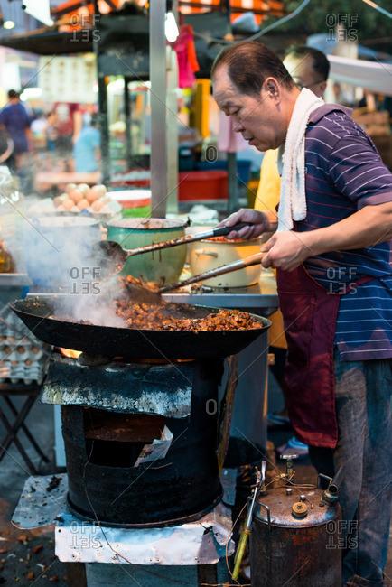 Kuala Lumpur, Malaysia - July 11, 2015: Man preparing traditional fried dish at Malaysian street market