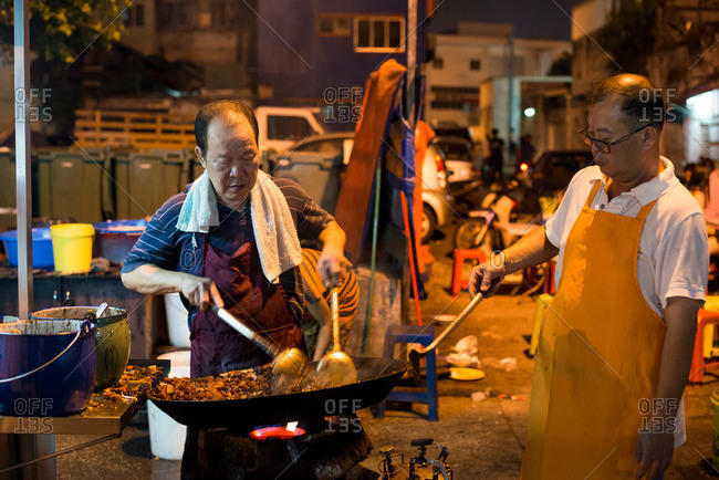 Kuala Lumpur, Malaysia - July 11, 2015: Two workers preparing traditional street food at outdoor market