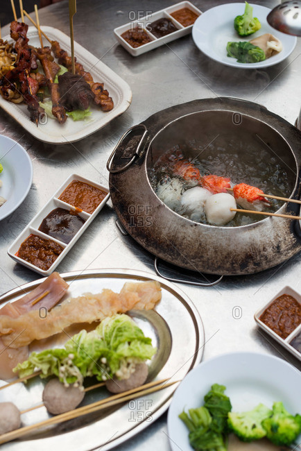 Skewered foods being cooked in a boiling pot at Malaysian hot pot stall