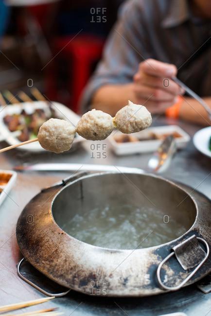 Placing skewered seafood balls at hot pot dining establishment