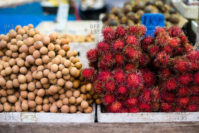 Close-up of fresh dates and rambutan at a Malaysian street market
