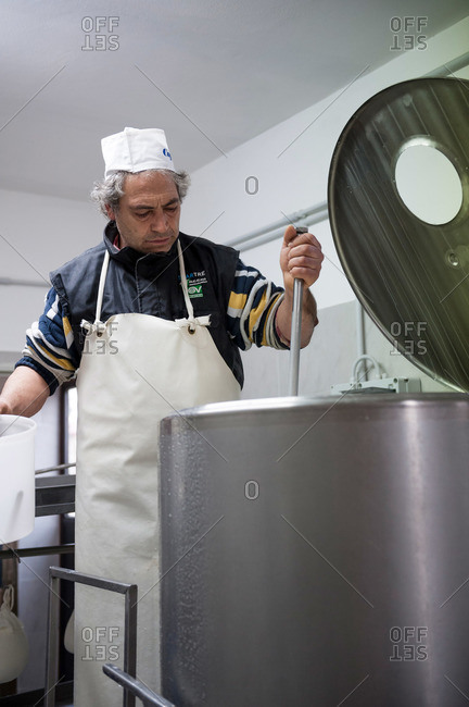 Tuscany, Italy - February 28, 2012: Man stirring ingredients in a pecorino cheese plant
