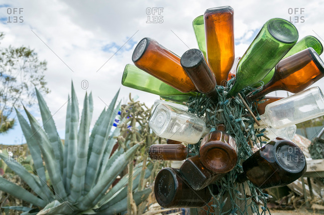 Glass bottles and string of lights decorating post
