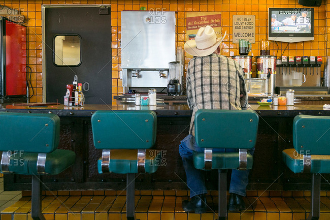 Victorville, California, USA - October 6, 2015: Cowboy watching TV in a diner