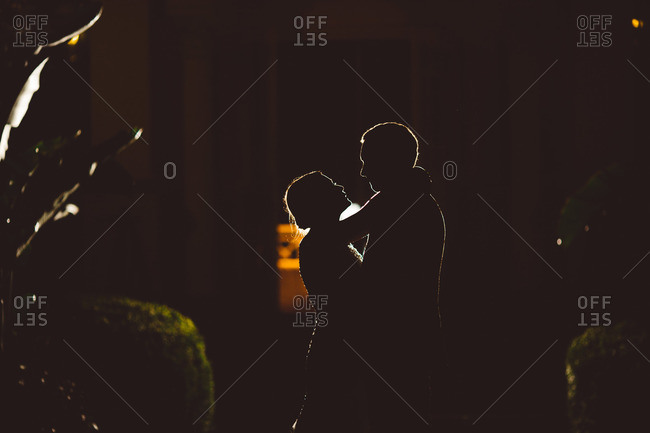 Silhouette of bride and groom embracing at night