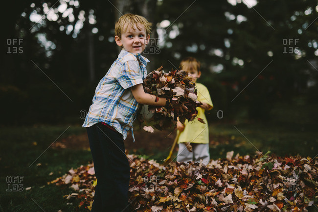 Two brothers playing in fall leaves