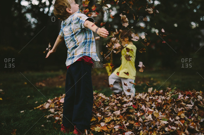 Two brothers tossing autumn leaves in the air