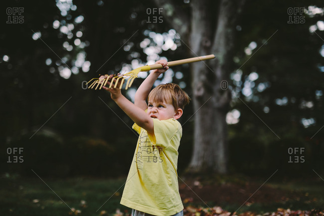 Little boy playing with a rake