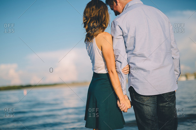 Couple holding hands near a lake