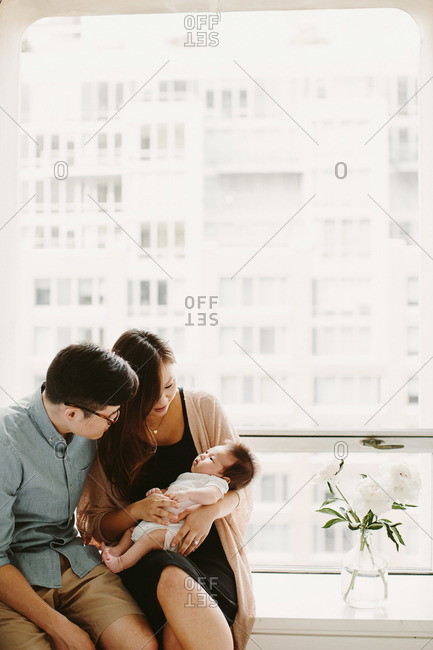 Couple sitting on windowsill gazing at their new baby