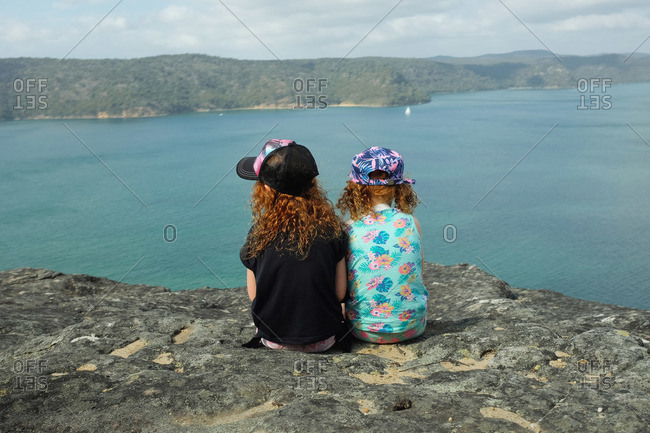 Two sisters sitting on a cliff at the Warrah lookout, Brisbane Water National Park, Patonga, Australia
