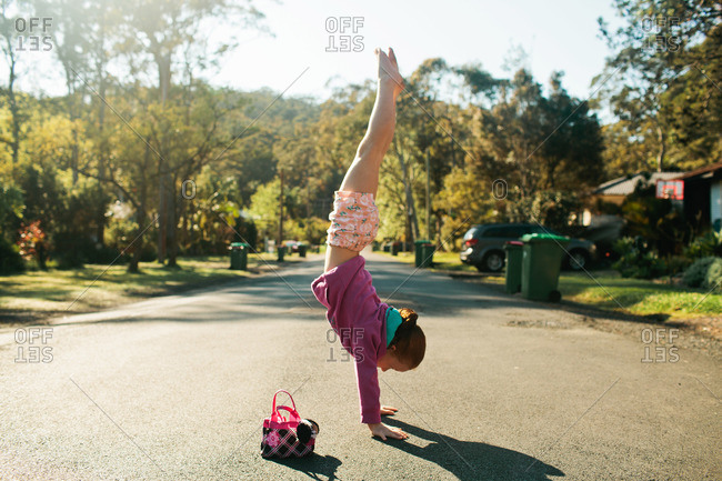 Little red head girl doing hand stand in the street