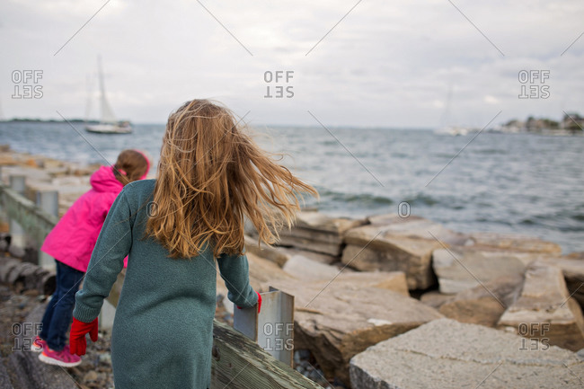 Two girls at a rocky harbor