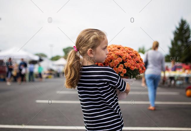A girl holds a pot of mums
