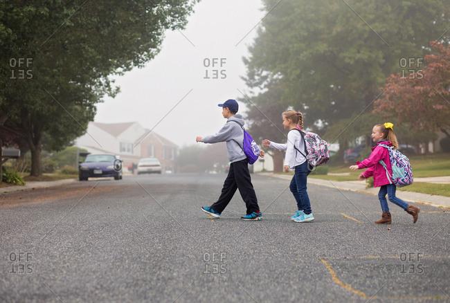 Three children cross a foggy street on the way to school