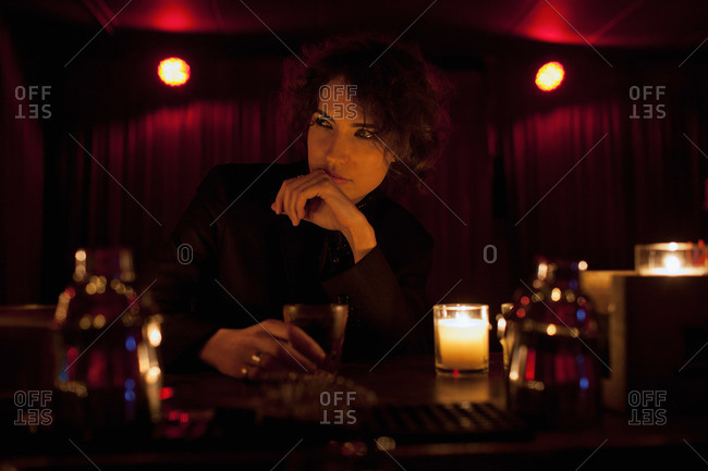 Woman sitting at a bar in a nightclub holding a drink