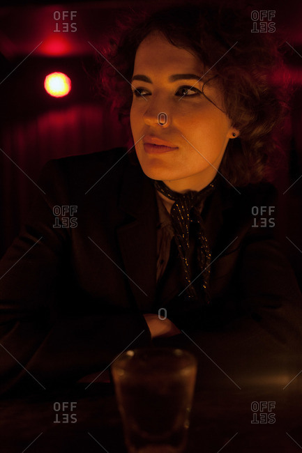 Woman sitting at a bar in a nightclub looking away