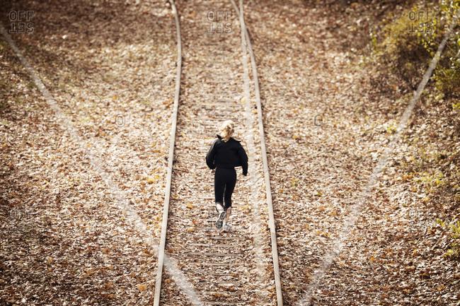 Female runner jogging down train tracks in fall